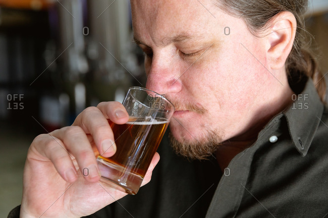 Close up of a Caucasian man with long hair working in a microbrewery, holding a glass of beer, smelling it for inspection.