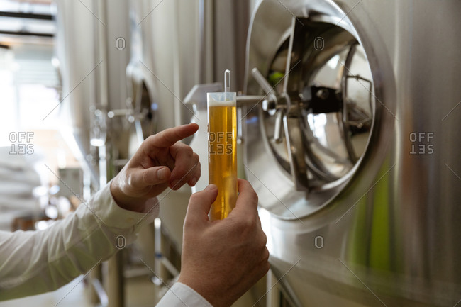 Mid section of a Caucasian man working at a microbrewery inspecting a glass of beer, checking its color, with vats in the background.