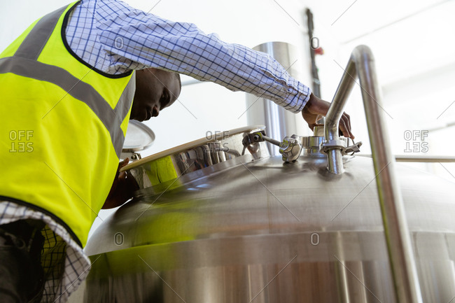 Low angle view of an African American man working at a microbrewery, wearing a high visibility vest, inspecting beer and looking inside the tank.