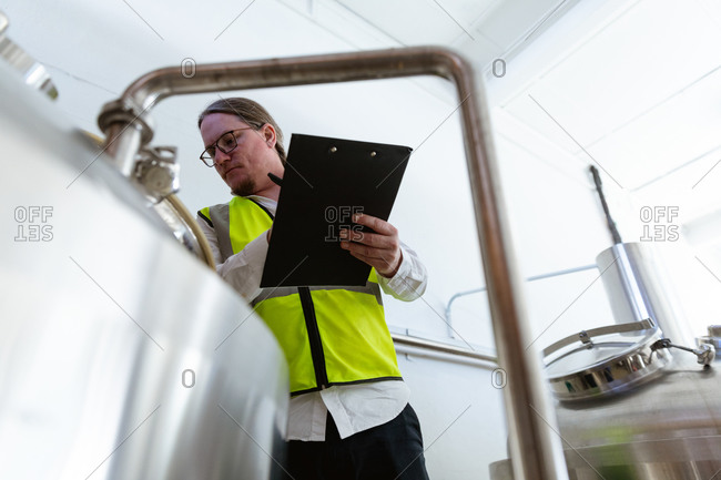Low angle view of a Caucasian man wearing high visible vest, working in a microbrewery, holding a file and writing data while checking vats.