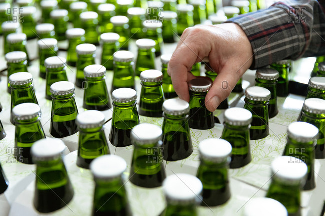 Close up mid section view of a Caucasian man working in a microbrewery, checking green glass bottles of beer ready for delivery.
