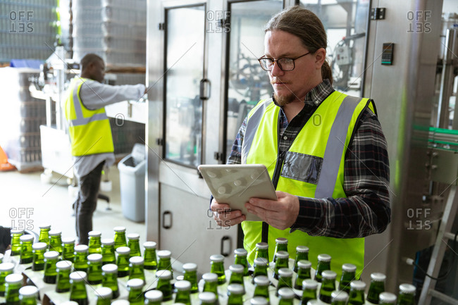 Caucasian man wearing high visibility vest, working in a microbrewery, using a tablet while checking bottles of beer prepared for delivery with an African American man working in the background.
