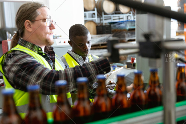 Caucasian man wearing high visibility vest, working in a microbrewery, checking bottles of beer with an African American man working in the background.
