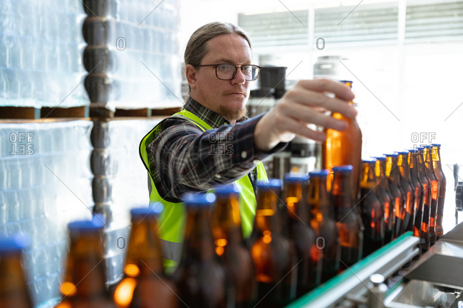 Caucasian man wearing high visibility vest, working in a microbrewery, checking dark glass bottles of beer on a conveyor belt.