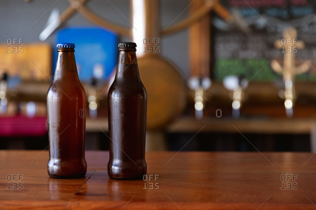 Two dark glass bottles with tops of beer sitting on the wooden bar at a microbrewery pub with taps in the background.