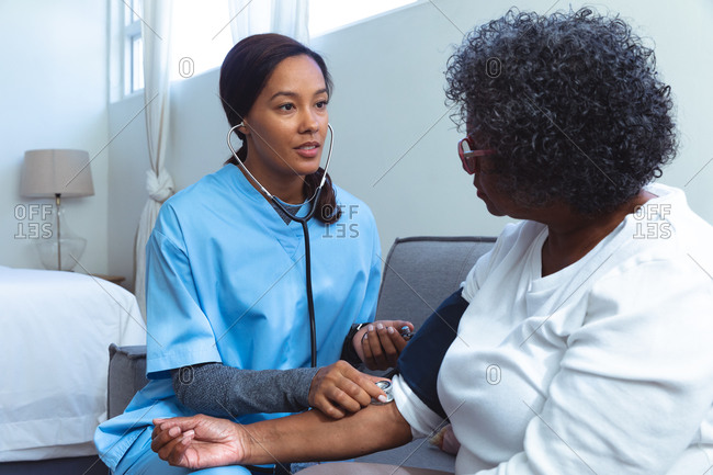 Senior mixed race woman spending time at home, being visited by a mixed race female nurse, the nurse taking blood pressure