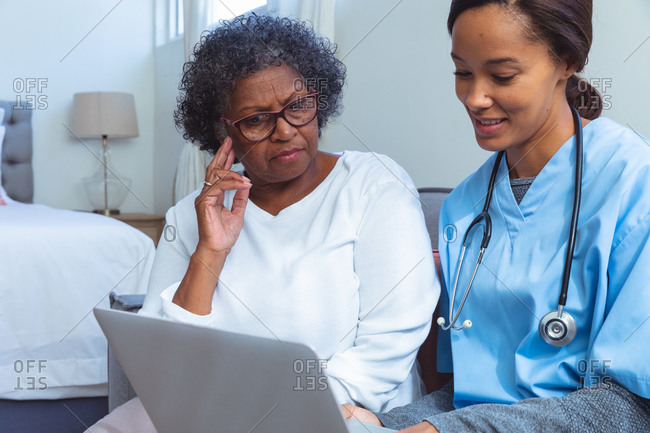 Senior mixed race woman spending time at home, being visited by a mixed race female nurse, the nurse using a laptop