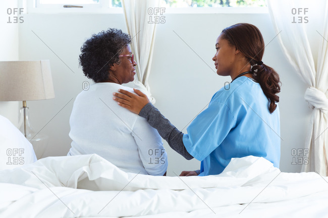 Senior mixed race woman spending time at home, being visited by a mixed race female nurse, sitting on a bed and talking