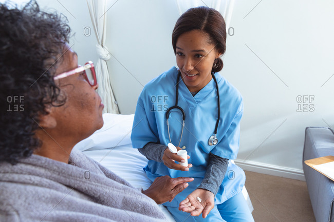 Senior mixed race woman spending time at home, being visited by a mixed race female nurse, the nurse giving her medicines