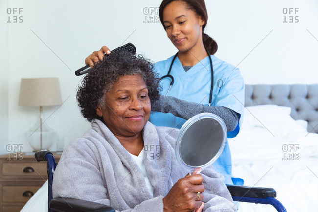 Senior mixed race woman spending time at home, sitting in a wheelchair, holding a mirror, being visited by a mixed race female nurse, the nurse, the nurse brushing her hair