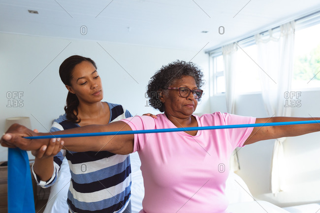 Senior mixed race woman spending time at home, being visited by a mixed race female nurse, the woman stretching her arms using elastic tape