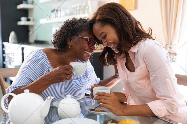 Senior mixed race woman spending time at home with her daughter, social distancing and self isolation in quarantine lockdown, having tea together and talking