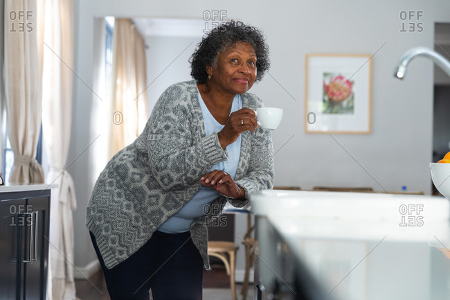 Senior mixed race woman enjoying her time at home, social distancing and self isolation in quarantine lockdown, standing in her kitchen, holding a cup and smiling