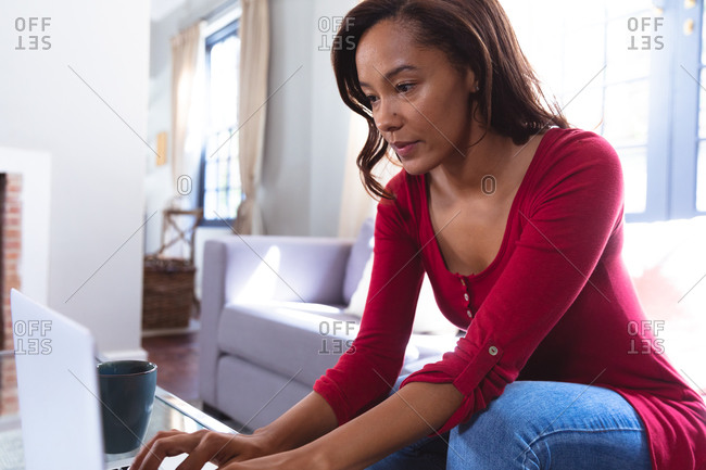 Mixed race woman enjoying her time at home, social distancing and self isolation in quarantine lockdown, sitting on a sofa, using a laptop
