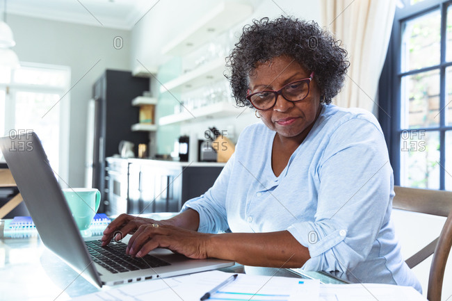 Senior mixed race woman enjoying her time at home, social distancing and self isolation in quarantine lockdown, sitting at a table, using a laptop