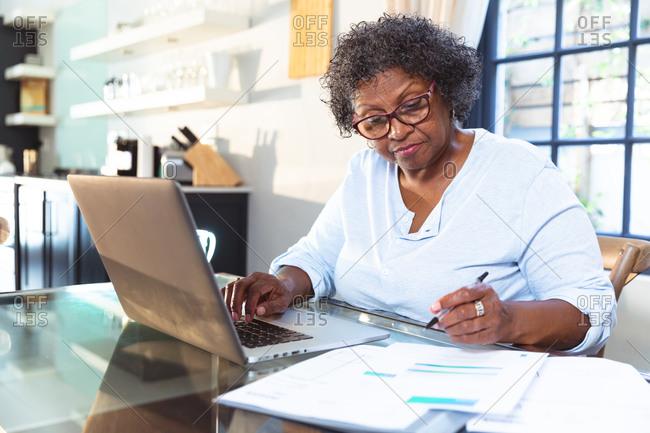Senior mixed race woman enjoying her time at home, social distancing and self isolation in quarantine lockdown, sitting at a table, using a laptop, doing paperwork