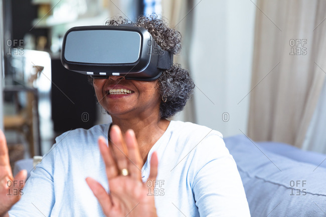 Senior mixed race woman enjoying her time at home, social distancing and self isolation in quarantine lockdown, sitting on a sofa, wearing vr goggles and touching virtual reality screen