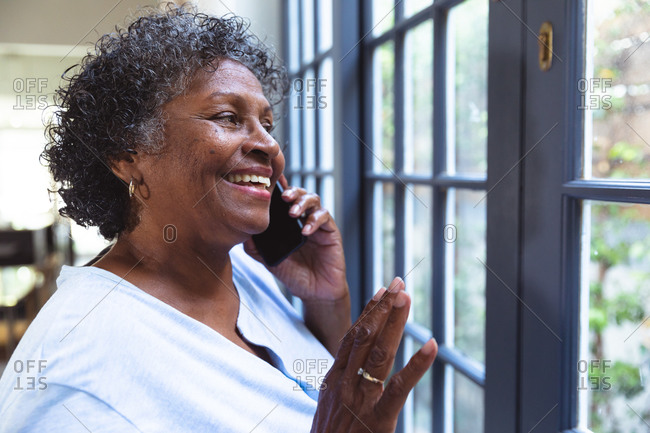 Senior mixed race woman enjoying her time at home, social distancing and self isolation in quarantine lockdown, looking through a window, talking on a smartphone