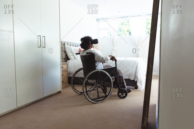 Senior mixed race woman enjoying her time at home, social distancing and self isolation in quarantine lockdown, sitting on a wheelchair, wearing vr goggles