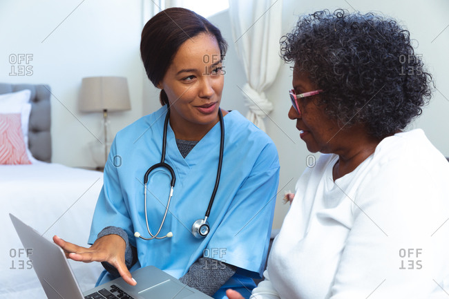 Senior mixed race woman spending time at home, being visited by a mixed race female nurse, using a laptop and talking