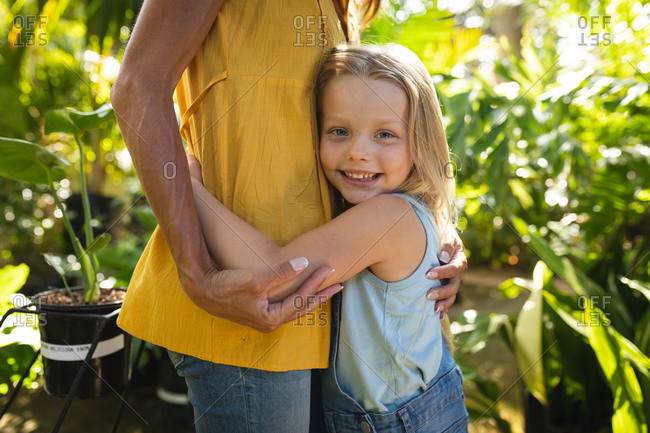 Mid section view of a Caucasian woman and her daughter enjoying time together in a sunny garden, embracing, the daughter looking at camera and smiling