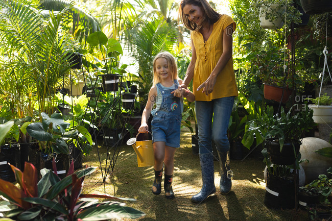 A Caucasian woman and her daughter enjoying time together in a sunny garden, looking at plants, the daughter holding a watering can