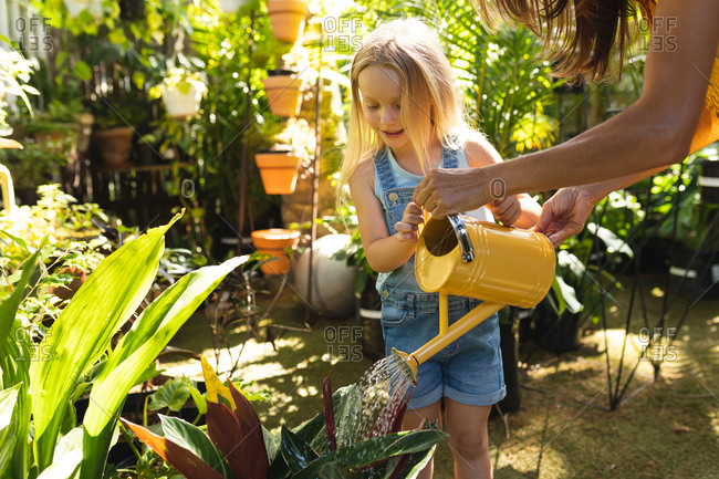 A Caucasian woman and her daughter enjoying time together in a sunny garden, looking at plants, watering plants with watering can