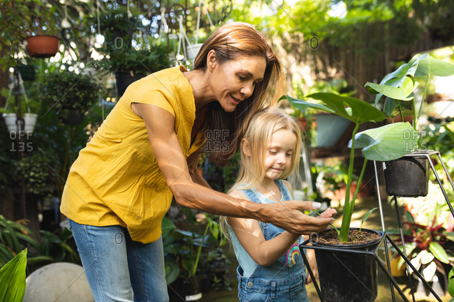 A Caucasian woman and her daughter enjoying time together in a sunny garden, looking at plants together and touching their leaves and flowers
