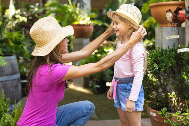 A Caucasian woman and her daughter enjoying time together in a sunny garden, woman kneeling and putting hat on her daughters head, smiling to each other