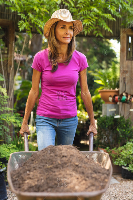 A Caucasian woman, enjoying time in a sunny garden, wearing a straw hat, pushing a wheelbarrow filled with earth and smiling