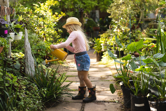 A Caucasian girl with long blonde hair enjoying time in a sunny garden, exploring, watering plants with watering can, wearing a straw hat
