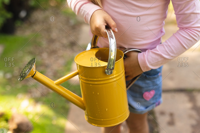 Mid section close up of a Caucasian girl enjoying time in a sunny garden, exploring, holding a yellow watering can