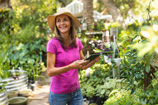 A Caucasian woman wearing a pink t shirt and a straw hat, enjoying time in a sunny garden, using a tablet computer