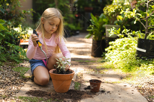A Caucasian girl with long blonde hair enjoying time in a sunny garden, exploring, planting a seedling in a pot, using garden fork