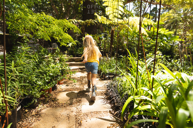 A Caucasian girl with long blonde hair, enjoying time in a sunny garden, running excitedly along a path between plants