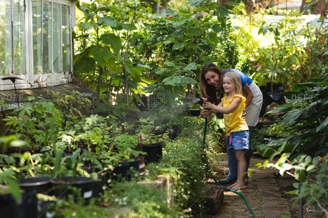 A Caucasian woman and her daughter enjoying time together in a sunny garden, using a garden hose to water the plants
