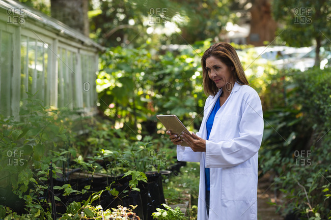A Caucasian woman with long brown hair wearing a lab coat, walking in a sunny garden, using a tablet computer