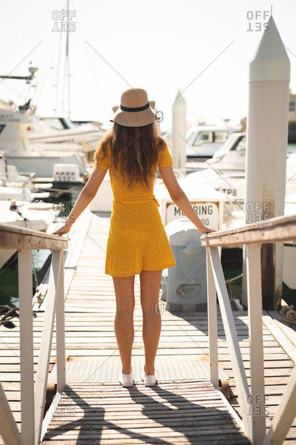 A teenage Caucasian girl, wearing a hat, enjoying her time on a promenade, on a sunny day,  leaning on a barrier, looking away