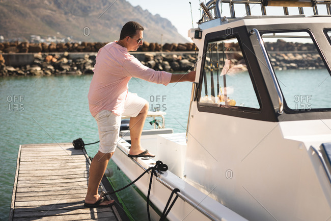 A Caucasian man, wearing a pink shirt, enjoying his time on a boat, on a sunny day, entering a sailing boat