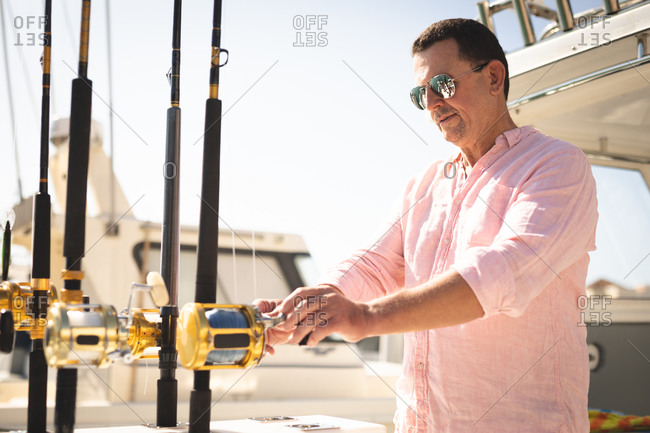 A Caucasian man, wearing a pink shirt and dark sunglasses enjoying his time on a boat, holding a fishing rod