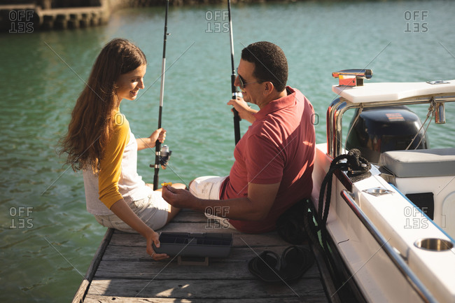 A Caucasian man and his teenage daughter enjoying time together on holiday in the sun by the coast, sitting on a jetty, holding fishing rods and talking