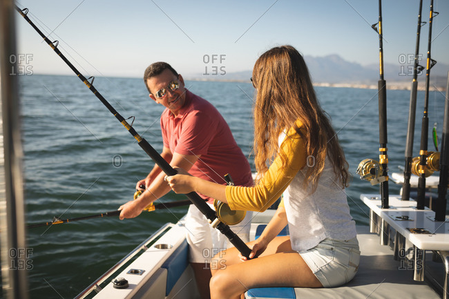 A Caucasian man and his teenage daughter enjoying time together on holiday in the sun by the coast, standing on a boat, holding and using fishing rods