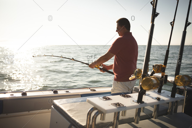 A Caucasian man enjoying his time on holiday in the sun by the coast, standing on a boat, holding a fishing rod