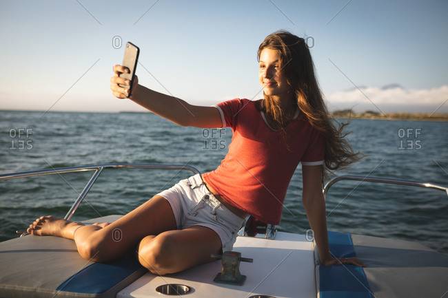A teenage Caucasian girl enjoying her time on holiday in the sun by the coast, sitting on a boat, taking a selfie