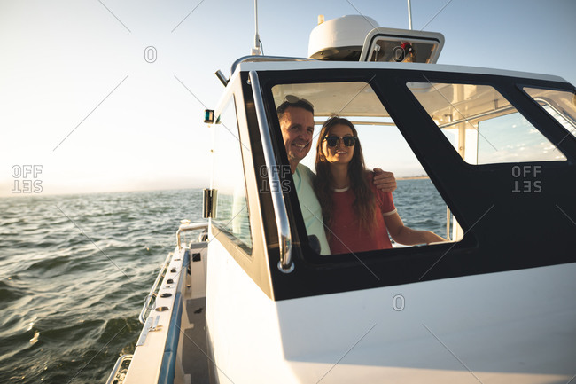 A Caucasian man and his teenage daughter enjoying time together on holiday in the sun by the coast, standing on a boat, looking through a window, embracing and smiling