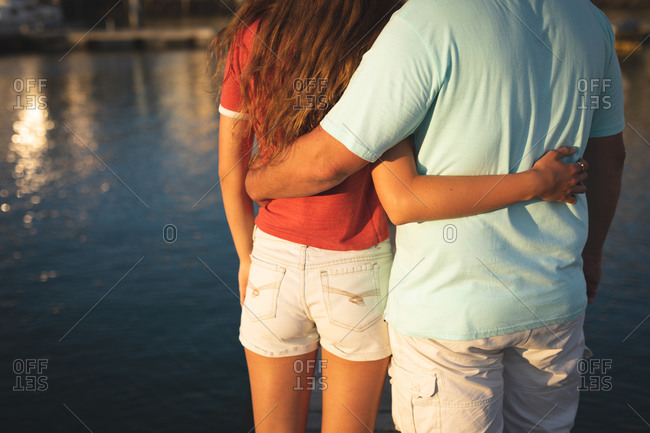 Mid section view of a Caucasian man and his teenage daughter enjoying time together on holiday in the sun by the coast, standing on a jetty, embracing