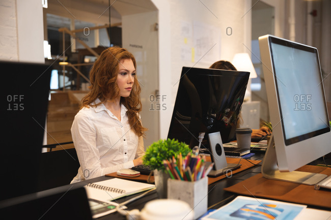 Caucasian female business creative working in a casual modern office, sitting at a desk and using a computer with a colleague working next to her