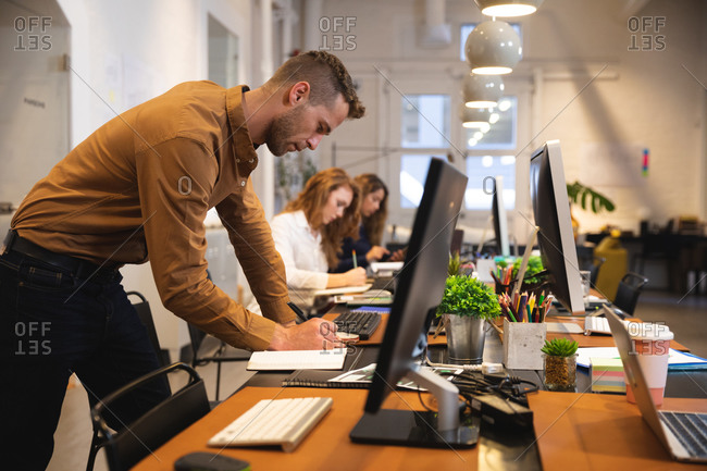 Caucasian male business creative working in a casual modern office, standing at a desk and taking notes with colleagues working in the background