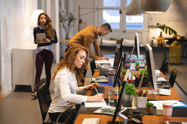Caucasian female business creative working in a casual modern office, sitting at a desk and using a computer with colleagues working in the background