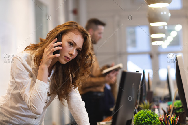 Caucasian female business creative working in a casual modern office, talking on a phone with colleagues working in the background